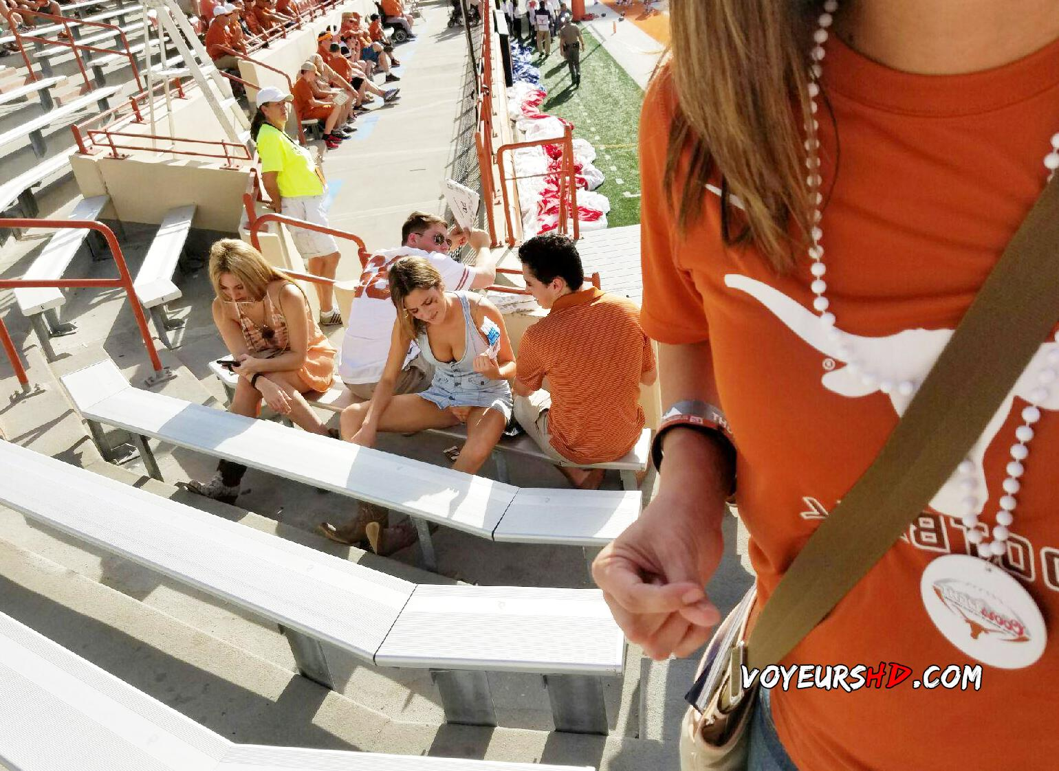 Voyeur notices hot girl with spread legs sitting on stadium bench and her upskirt is visible