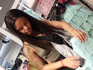 Tattooed beauty with dark hair is shopping for clothes