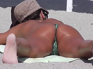 Voyeur zooms on tight bronze tanned ass on beach