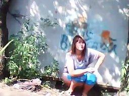 Women pee behind an old wall