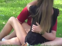 Young horny couple on the park grass
