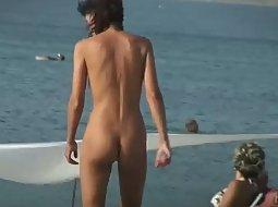 Skinny nudist girl arranges towels