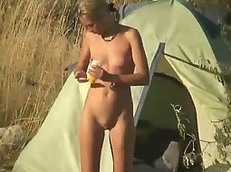 Nudist girl rubbing oil on her body