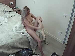 Spying on young woman rubbing lotion on her naked body