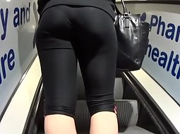 Sporty babe on the moving stairs