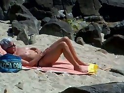Girl oiles her body on the beach
