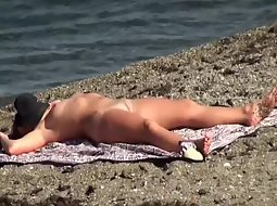 Hot woman sunbathing on a beach