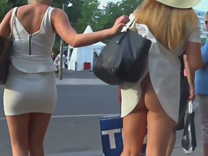 Fancy blonde lifts friend's skirt and shows naked ass