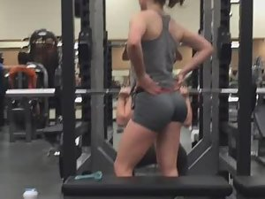 Fit girl squats and spots her friend in gym