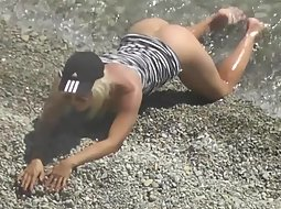 Sexy chick is half nude at the beach