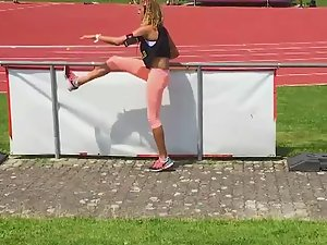 Athletic girl warms up by the fence