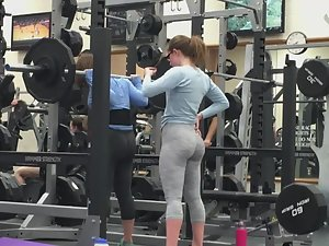 Sexy sisters doing squats in gym