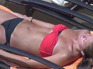 Hot body of a girl sunbathing by the swimming pool