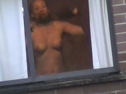 Blonde lady dresses up near window